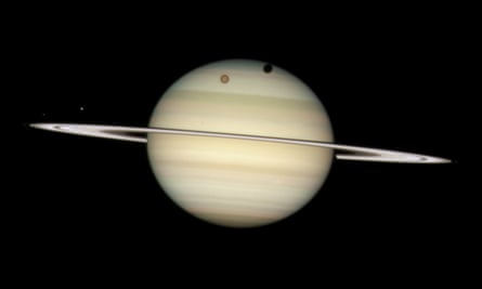 The giant orange moon Titan casting a large shadow on to Saturn's north polar hood