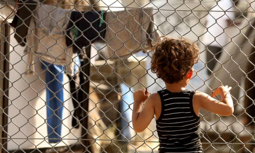 A child looks through a fence at the Moria refugee camp on the Greek island of Lesbos