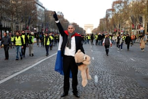 A demonstrator with a French flag holds a teddy bear on the Champs Élysées