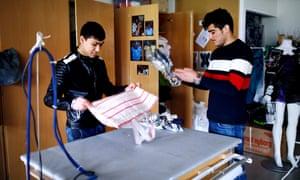 Samir, left, and Noor making bags