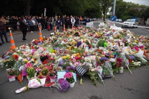 People gather next to floral tributes in Christchurch.