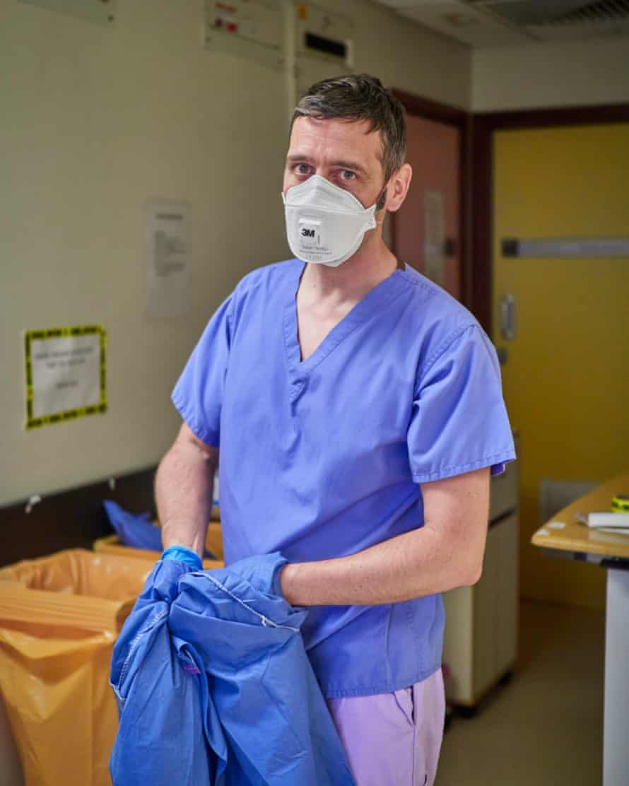 Paul Taylor, a former ICU nurse who returned to offer his experience and skill and support his colleagues, removing PPE at the end of a long shift.