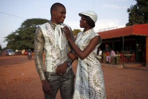man and woman in matching, light coloured bazin outfits