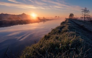 """Misty River Dawn by Kevin Pearson. """"My image was taken in late April along the bank of the River Brue in Glastonbury, Somerset. The flat, open, exposed landscape of the Somerset levels is punctuated by drainage channels and waterways which gives it a unique character. Cool evenings when followed by clear mornings tend to give rise to a blanket of mist rising off the water and grassland, creating an ethereal feel to the landscape especially at sunrise before the mist burns away. You can see the frost still clinging to the grassy riverbank."""""""
