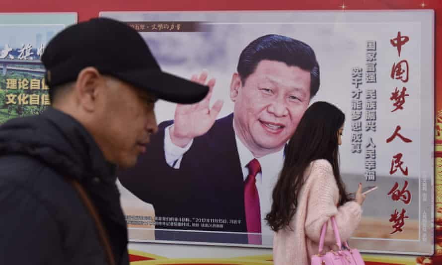 People walk past a poster of Chinese President Xi Jinping beside a street in Beijing. The Communist party has paved the way for him to assume the presidency indefinitely.