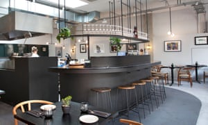 The curved gunmetal-grey bar, with stools around it and glasses on a shelf suspended from the ceiling at Cornerstone