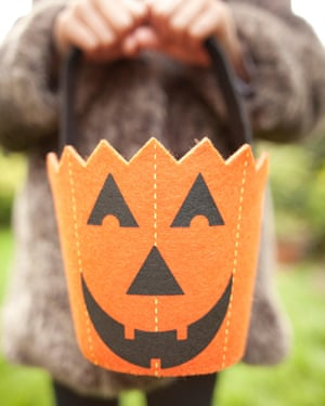 A girl holding up a halloween pumpkin bag for trick or treating
