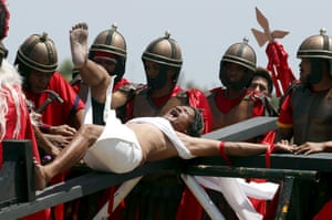 Roman soldiers re-enact the crucifixion with penitent Ruben Enaje near San Fernando, Phillipines