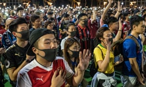 Pro-democracy demonstrators hold their phones in the air and form a human chain in Victoria Park, Hong Kong. Security forces have not managed to quell the protests since they erupted this summer.