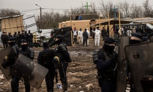 French police stand guard near makeshift places of worship at the migrant camp in Calais.