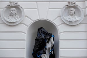A statue is covered with black bags during the restoration of the National Theatre in the old town. The theatre is a Unesco world heritage site