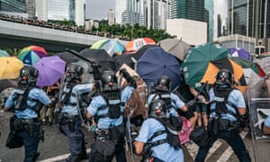 Protesters use umbrellas to defend themselves against police batons during a clash outside the Legislative Council Complex.