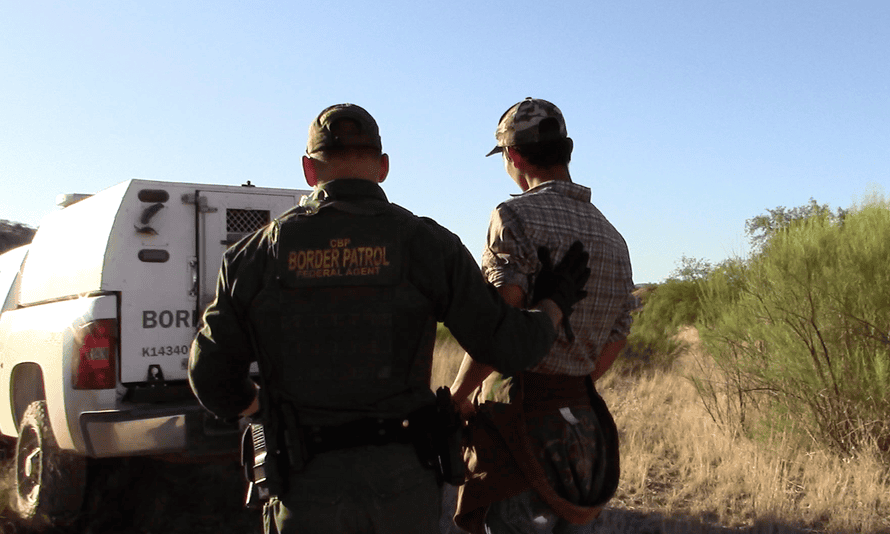Border patrol officers arrest migrants at a humanitarian aid camp in the Arizona desert.