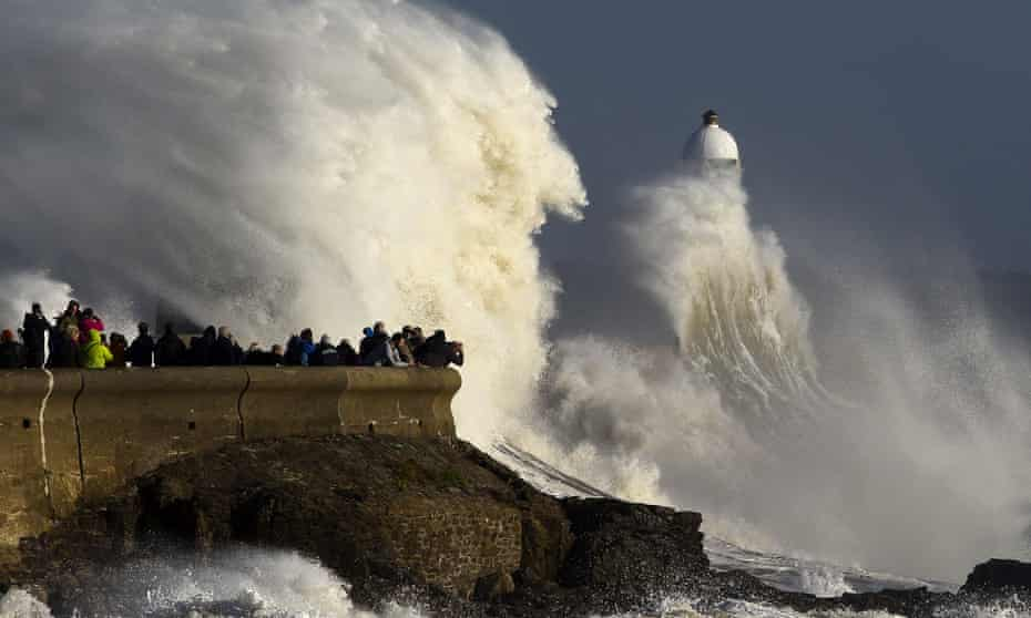Waves lash the harbour wall and lighthouse at Porthcawl, south Wales.