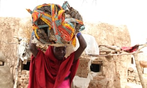 A  young girl from Niger carries animal dung on her head to sell at a local market.