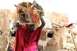 A young girl from Niger carries animal dung on her head to sell at a local market