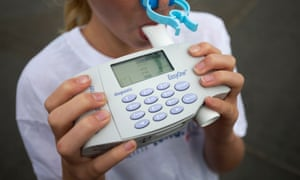 A young girl blows into a spirometer during a photocall to promote clean air in London.