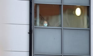 A person wearing a face mask looks out from a window of the accommodation block at Arrowe Park hospital in Wirral.