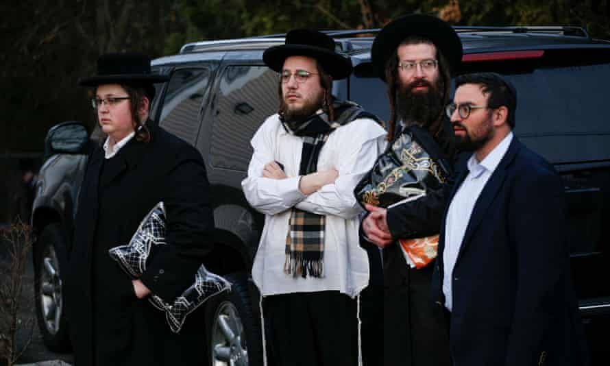 Members of the Jewish community gather outside the home of rabbi in Rockland county on Sunday.