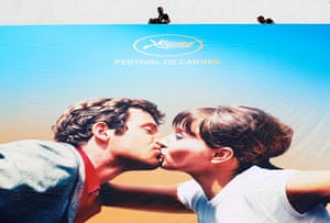 Workers set up the official poster of the 71st annual Cannes film festival, displaying Belmondo and Anna Karina in Pierrot le Fou, on the Palais des Festivals, Cannes, 6 May 2018.