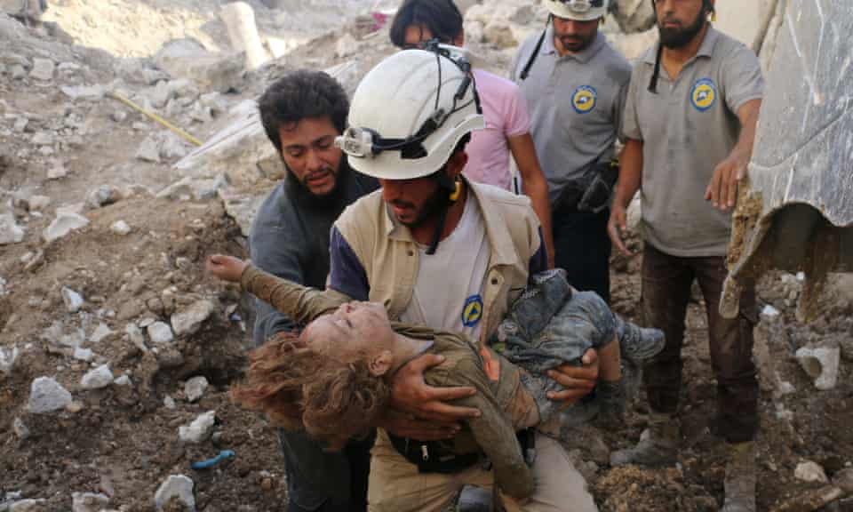 A member of the White Helmets, also known as the Syrian civil defence, holds a child pulled from the rubble following an airstrike in Aleppo in 2016.