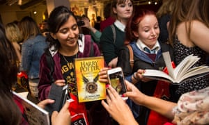 Customers take photos after buying a copy of JK Rowling's Harry Potter and The Cursed Child a little after midnight at Foyles book store in London.