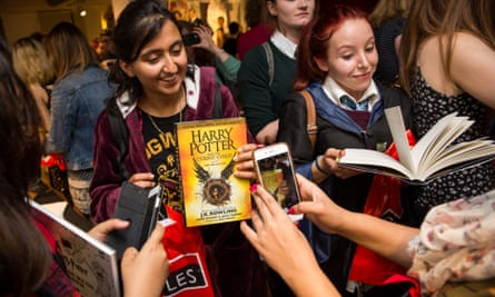 Customers take photos after buying a copy of JK Rowling's Harry Potter and The Cursed Child at midnight on 31 July, in Foyles bookstore in London.
