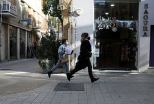 Two women wearing protective masks run in Ledra Street, a main shopping street, in Nicosia, Cyprus on 8 January, 2021.
