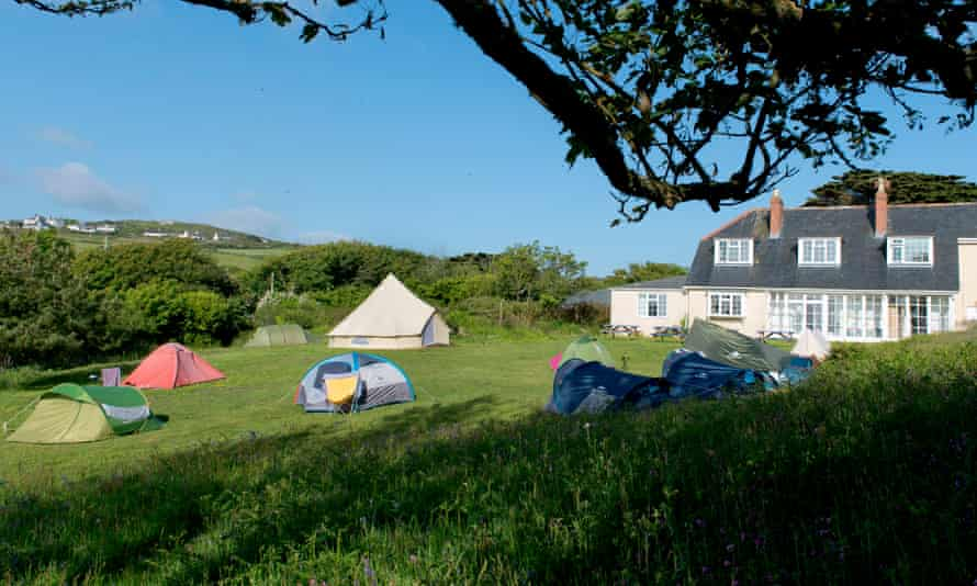 YHA Land's End, exterior image of field, tents and YHA building, Cornwall, UK.