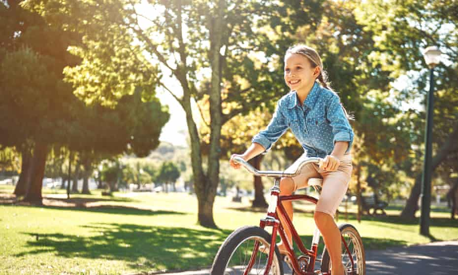 A little girl out for a ride on her bike in the park