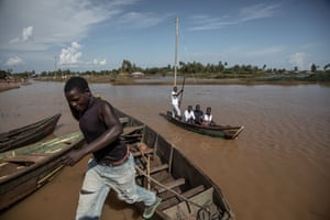 A man jumps from a boat in flooded Busia county.