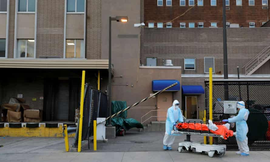 Workers wheel a body from the Wyckoff Heights medical center during the coronavirus outbreak in New York. Trump has told governors to find life-saving equipment on their own.