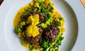 Meatballs in a yellow sauce with green broccoli