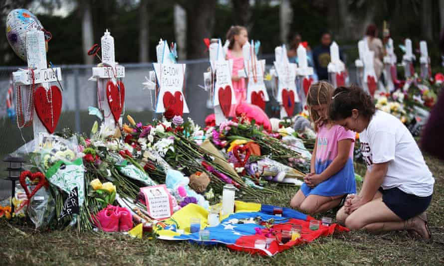 People visit a makeshift memorial in front of Marjory Stoneman Douglas High School, five days after the February shooting.