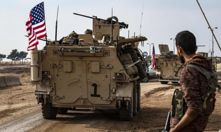 A fighter stands on the side of a road as a convoy of US troops drives by in Qamishli, in Syria's Hasakeh province.