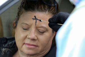 A woman receives ashes at the drive-through service in Metairie