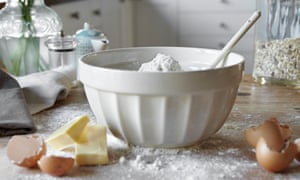 Bowl of mixing dough in messy kitchen.