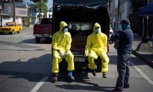 Funeral home workers wearing protective gear wait beside a coffin in a truck outside of Teodoro Maldonado Carbo Hospital amid the spread of the coronavirus disease in Guayaquil, Ecuador 3 April, 2020.