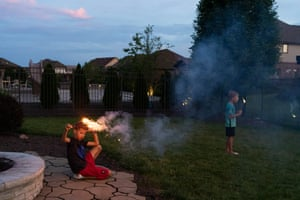 Joey and Jackson play with sparklers during an early Fourth of July celebration in their backyard.