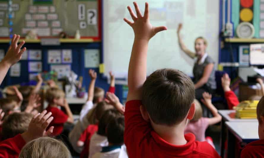 Children at a school raise their hands