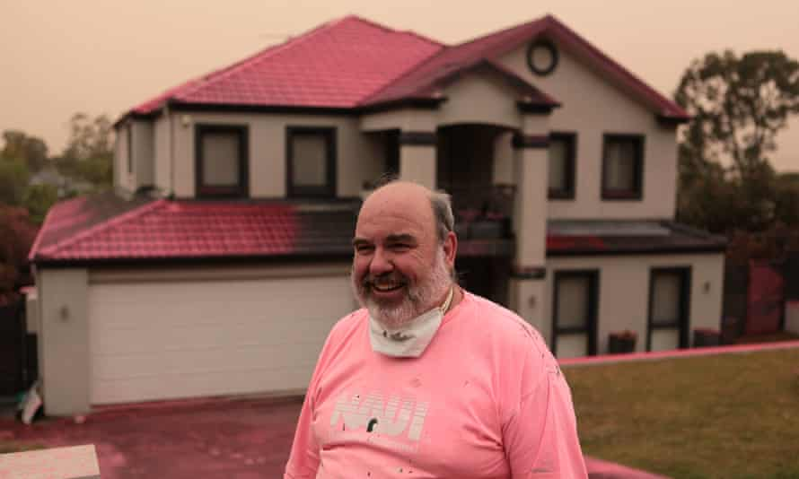 Douglas Greening stands outside his neighbour's house, covered in fire retardant dropped from aircraft on Canoon Road, South Turrumurra