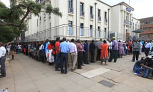Zimbabweans queue to withdraw cash in Harare after a severe shortage of US dollars which are used as local currency.