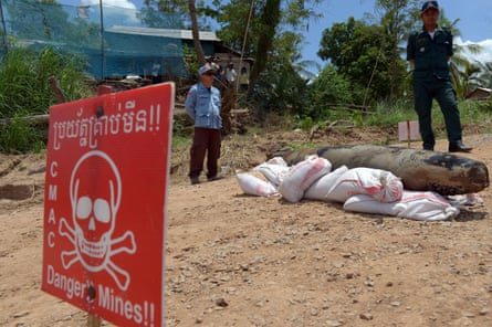 A Cambodian mine action centre member, left, and policeman keep watch behind a Mark 82 bomb in Kandal province.