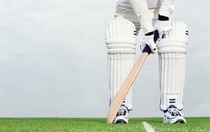 Cricket batsman preparing to bat, seen from waist down