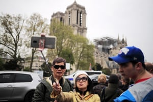 Tourists take a selfie near the damaged Notre Dame Cathedral