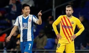 Wu Lei celebrates Espanyol's second goal while Barcelona's Jordi Alba looks on dejectedly.