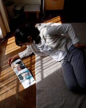 Nao Niitsu looks at BTS's photo book in her room in Tokyo