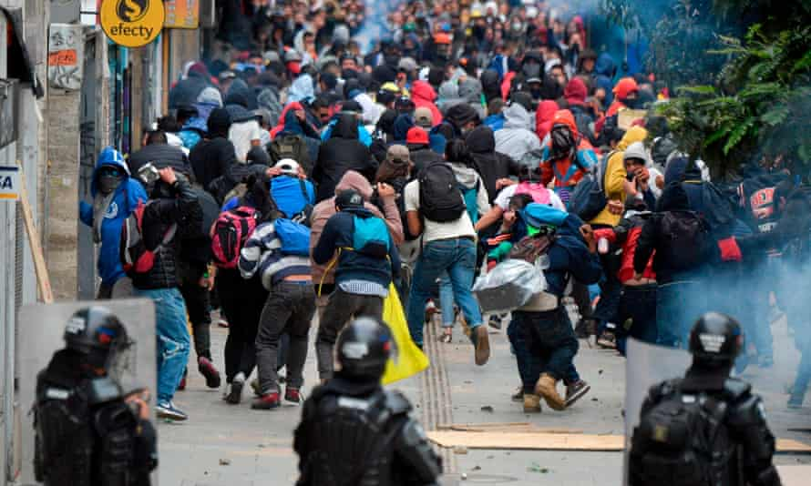 Protesters and riot police clash in Bogota, Colombia, on Friday