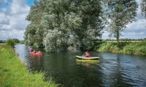 Two canoeists on the River Waveney on a blue-sky day.