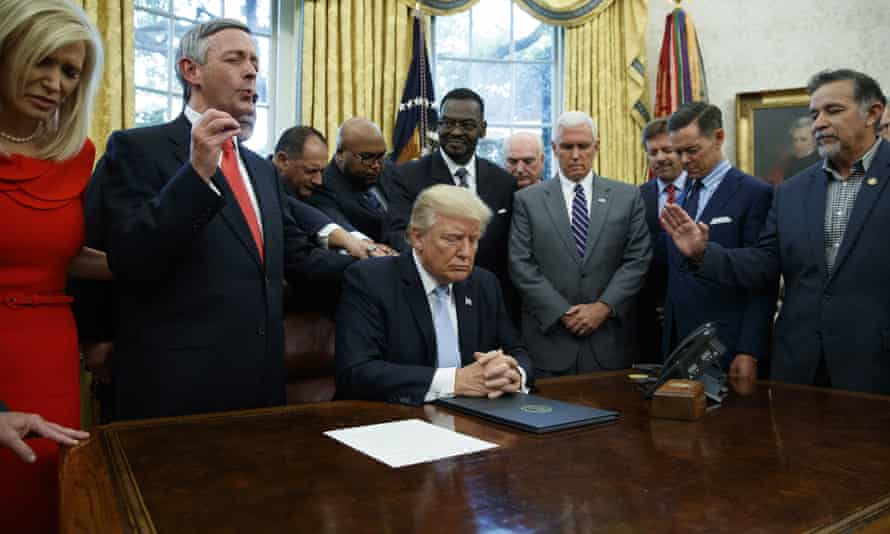 Religious leaders pray with President Trump in September 2017. The aid effort is seen as a sop to Christian evangelicals in his base.